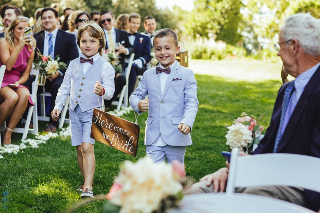Ring bearers carrying the here comes the bride sign into the wedding ceremony.
