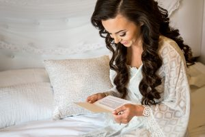 Sacramento Wedding Photographer - beautiful Bride in white robe reading Groom's note
