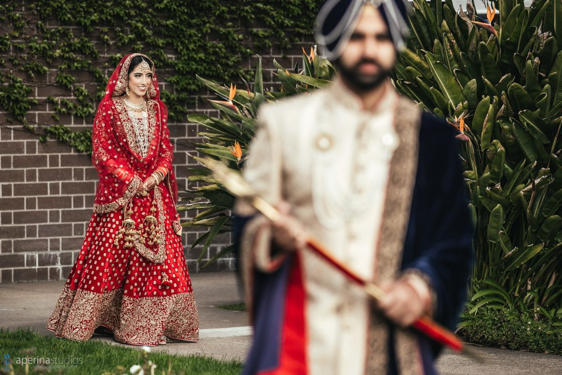 Indian bride in red lehenga and groom first look in a rooftop garden.