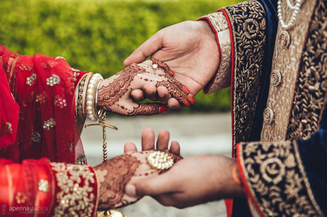 Indian bride in red lehenga and groom hold hands decorated with henna and gold rings and jewelry