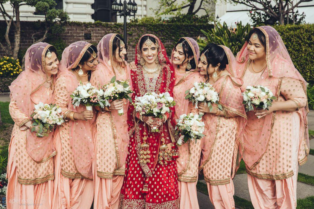 Indian bridesmaids in red and peach lehengas on the rooftop garden of Fairmont San Francisco cityscape