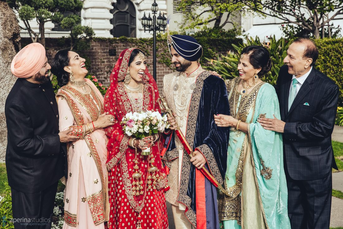 Indian bride in red lehenga with family on the rooftop garden of Fairmont San Francisco cityscape