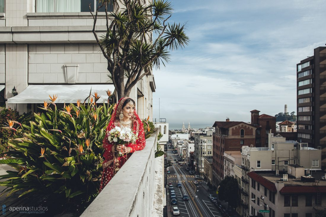Indian bride in red lehenga portrait on the rooftop of Fairmont San Francisco cityscape
