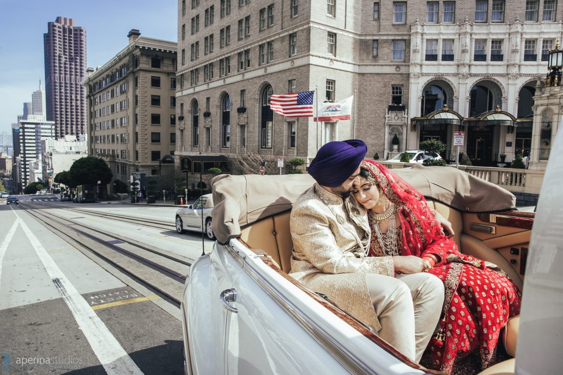 Indian wedding couple driving in antique car through the City of San Francisco