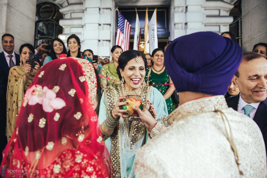 Sikh Indian wedding tradition welcoming bride in red lehenga into family