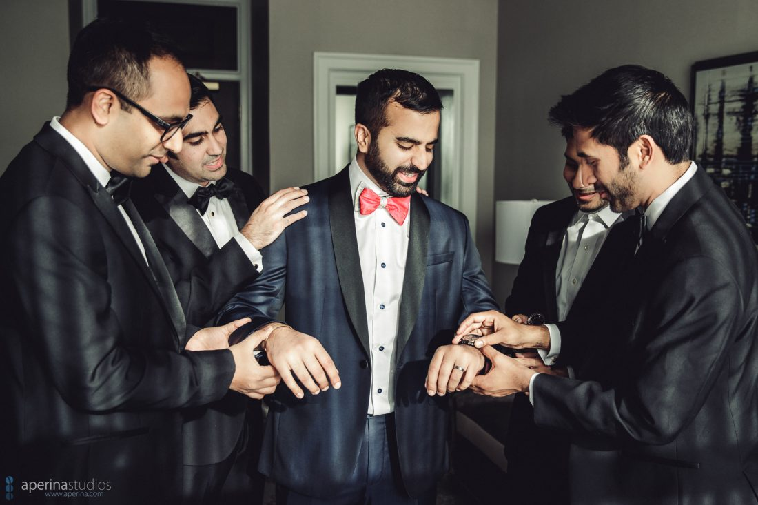 Indian groom getting dressed for wedding reception in tuxedo with groomsmen with red bowtie