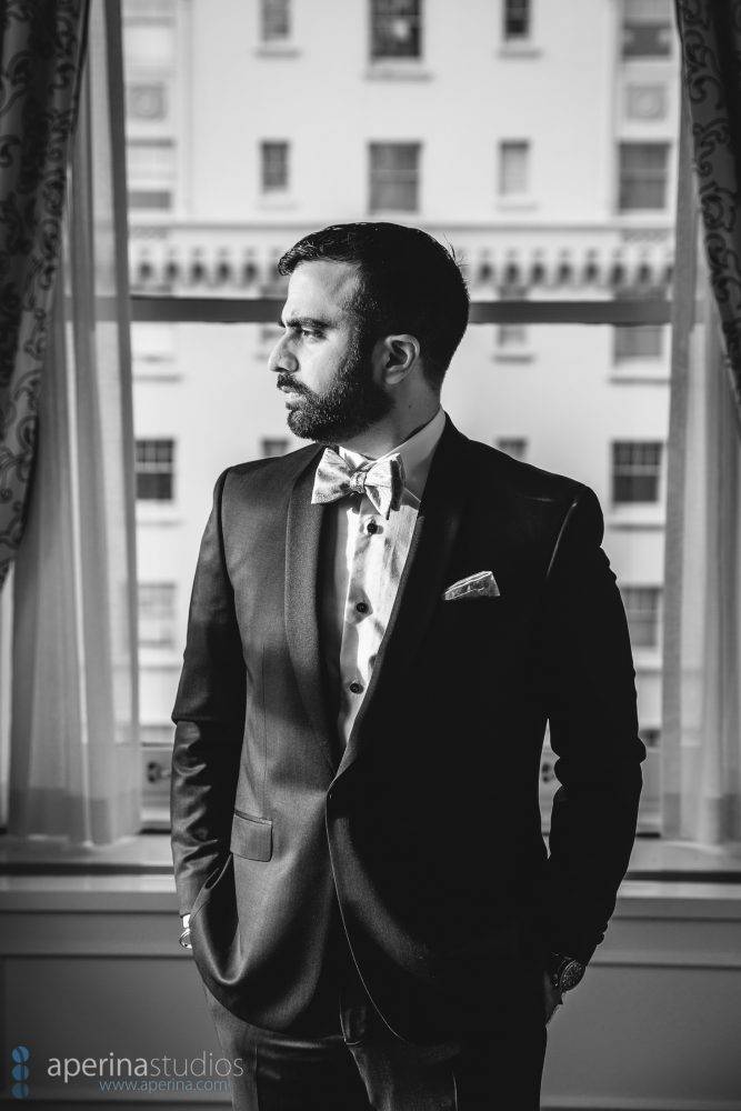 B&W image of Indian groom posing by a window in a tuxedo
