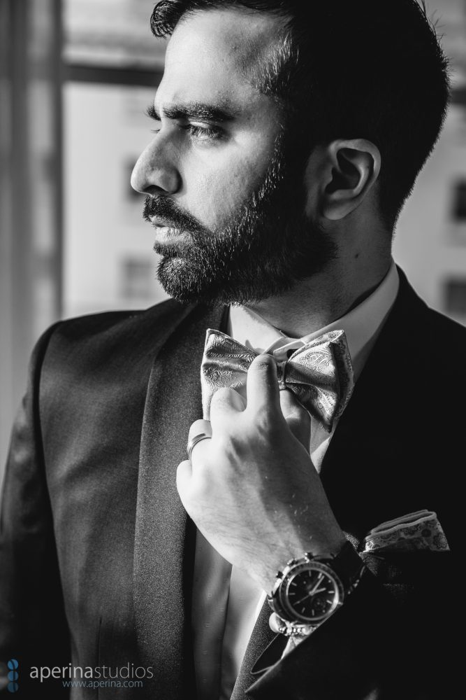 B&W image of Indian groom posing by a window in a tuxedo and bowtie