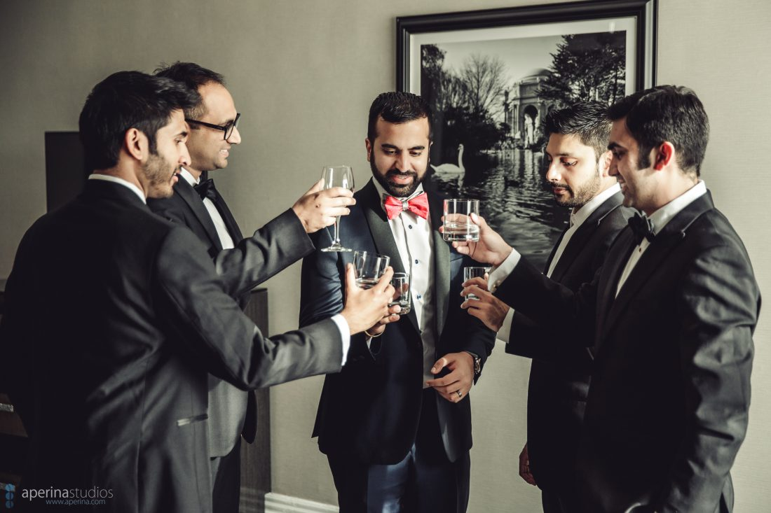 Indian groom and groomsmen cheers before reception in tuxedo with red bowtie