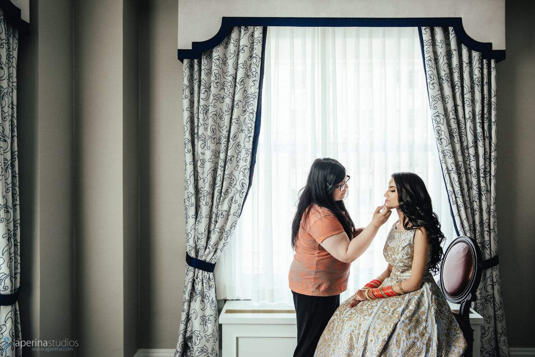 Indian bride getting makeup done in hotel room of Fairmont SF