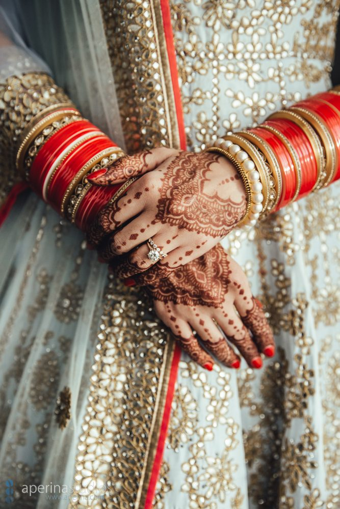 Indian bride model in Pratap Sons wedding dress and gold jewelry on henna mehndi hands