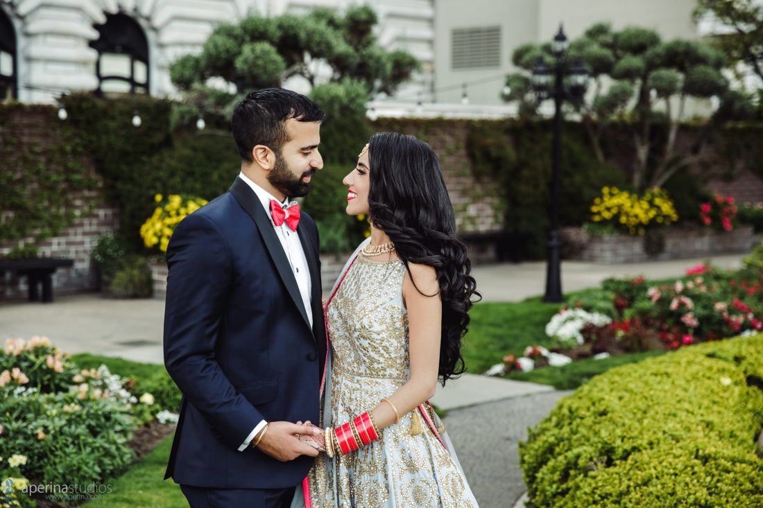 Indian bride in Pratap Sons wedding dress and gold jewelry and groom with red bowtie portrait