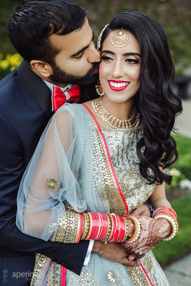 Indian bride in Pratap Sons wedding dress and gold jewelry and groom with red bowtie candid portrait