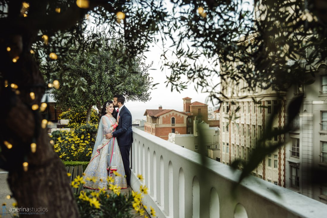 Indian bride in Pratap Sons wedding dress and gold jewelry and groom in navy blue tuxedo with red bowtie rooftop Fairmont SF portrait