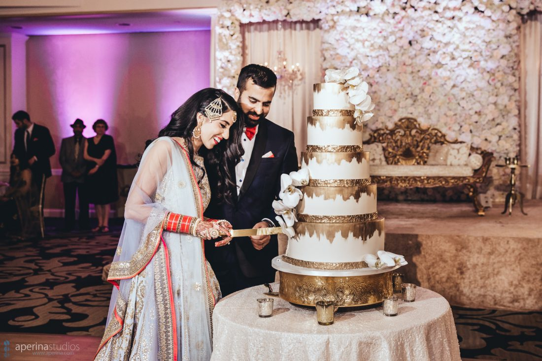 Indian wedding reception bride and groom cutting 5 layer gold cake in the grand ballroom of Fairmont SF
