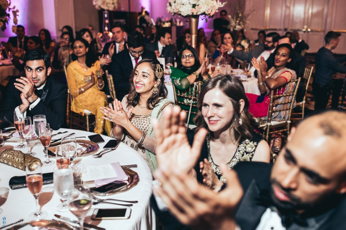 Indian wedding reception formally dressed guests clapping and happy