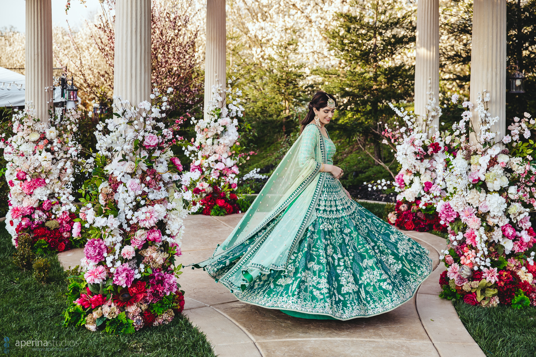 Indian Bride twirling while wearing stunning blue and green Anita Dongre lehenga on her Sangeet