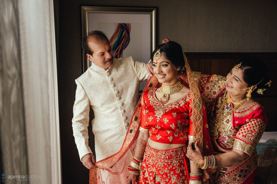 Indian wedding photography - Bride getting ready in red lehenga dress.