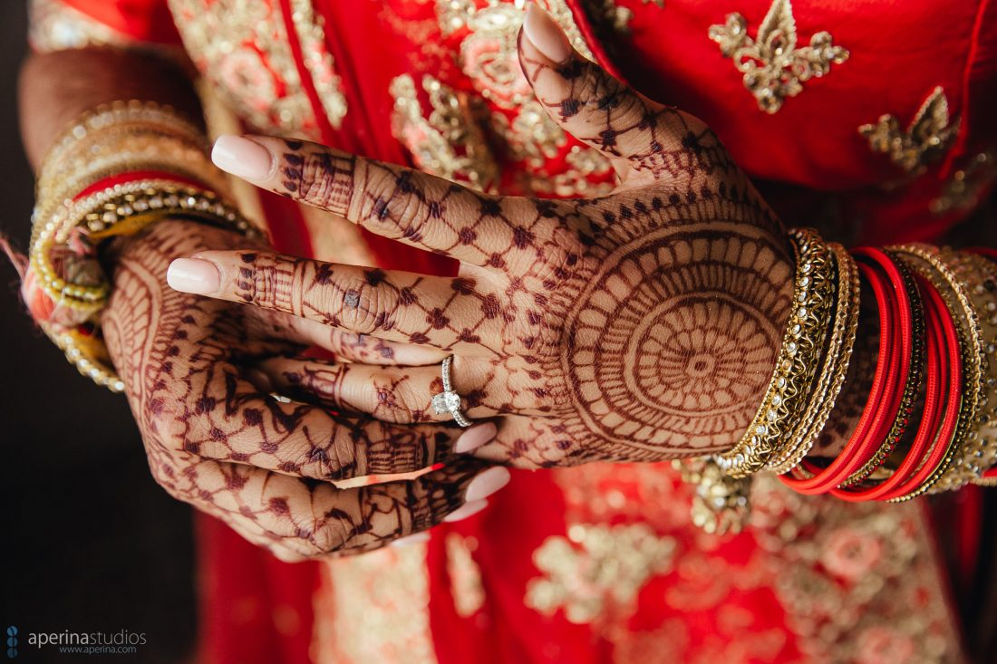 Indian wedding photography - Bride fixing diamond ring in red lehenga dress.